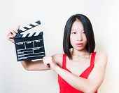 picture of neutral  - Young beautiful asian woman portrait with neutral look and red dress holding movie clapperboard on white background - JPG