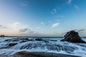 picture of shoreline  - Ocean water rushing over rocky shoreline with large rock in foreground - JPG
