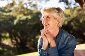 stock photo of close-up middle-aged woman  - attractive middle aged woman sitting at the park - JPG