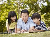 stock photo of lie  - asian father and children lying on grass reading a book together in a park - JPG