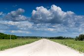 image of dirt road  - Empty dirt road leads into the horizon as white clouds gather overhead - JPG