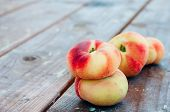 pic of saturn  - Fresh Saturn peaches on old wooden background - JPG