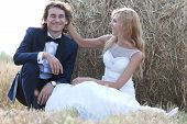 stock photo of she-male  - Young married couple having fun beside a hay bale - JPG