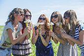 stock photo of dandelion seed  - Girls girlfriend inflate dandelion seeds in the wind in summer - JPG