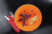 stock photo of black-cherry  - grilled beef meat with berries fried potatoes and cherry under sweet honey sauce on orange plate over black wooden table - JPG