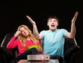 pic of watching movie  - Young couple watching movie or sport broadcast on tv sitting on sofa in living room - JPG