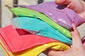 stock photo of holi  - holi multicolor paint dust packs in hands - JPG