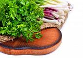 stock photo of rocket salad  - Parsley green onion garlic rocket salad on cutting board isolated on white - JPG