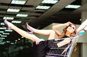 pic of trolley  - One young pretty fashion girl in black dress sitting in shopping trolley indoor on store backdrop horizontal picture - JPG