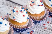 image of sprinkling  - Cupcakes with patriotic 4th of July sprinkles on vintage background shallow depth of field - JPG