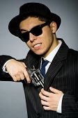 stock photo of top-gun  - Young man in classic striped costume holding gun isolated on gray - JPG