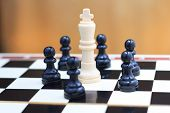 picture of chessboard  - White king and black pawns on the chessboard closeup - JPG