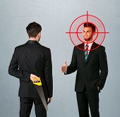 stock photo of backstabbers  - Ruthless businessman handshake with a hiding weapon and a head target point - JPG