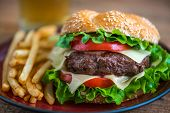 picture of hamburger  - Closeup of Homemade Hamburger with Fresh Vegetables and French Fries on a Plate - JPG