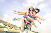stock photo of mans-best-friend  - Happy hipster couple in love on airplane travel honeymoon vacation  - JPG