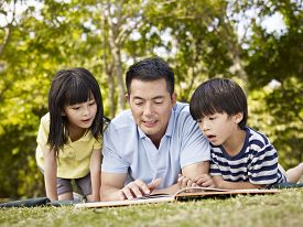 stock photo of japan girl  - asian father and children lying on grass reading a book together in a park - JPG