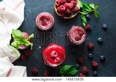 Fresh raspberry fruit drink in glass jar decorated by mint leaves and berries . Detox, diet or healt