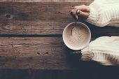 Woman holding cup of hot coffee on rustic wooden table, closeup photo of hands in warm sweater with  poster