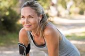 Portrait of athletic mature woman resting after jogging. Beautiful senior blonde woman running at th poster