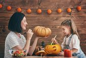 Happy halloween A mother and her daughter carving pumpkin. Happy family preparing for Halloween. poster