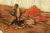 stock photo of brahma-bull  - Spurs gloves bells and chaps resting on hay bales - JPG