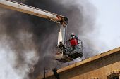 image of boom-truck  - Firefighter on the firetruck boom during fire - JPG