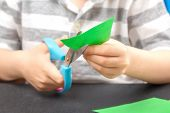Cutting Out Of Colored Paper. A Child With An End-point Scissors Cuts Green Paper. The Concept Of Ch poster