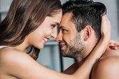 Sensual Smiling Couple Touching With Foreheads And Looking At Each Other At Home poster