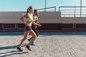 Pretty Sporty Woman And Man Jogging At City At Morning. Fit Fitness Young Caucasian Girl And Boy Run poster