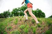 The Girl Is Running On Rough Terrain. A Woman Is Running On The Grass. Jogging. Active Lifestyle. En poster