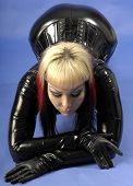 foto of domina  - fetish model wearing black latex against a blue background - JPG