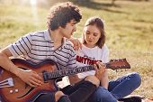 Outdoor View Of Lovely Female And Her Male Companion Have Leisure Time, Handsome Teenager Plays Guit poster
