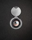 stock photo of peep hole  - Human eye in peep hole closeup - JPG
