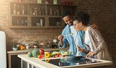 Happy African-american Couple Preparing Dinner In Loft Kitchen At Home. Family Cooking Healthy Food poster