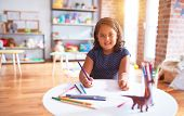 Beautiful toddler girl drawing cute draw using colored pencils at kindergarten poster