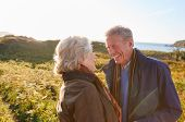 Loving Active Senior Couple Walking Along Coastal Path In Autumn Together poster