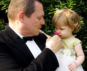 picture of flower girl  - man in tux with baby daughter smelling a rose - JPG