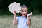 Idea. Pretty thinking little girl posing summer nature outdoor with cloud of thoughts (like in comic poster