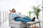 Young Man Relaxing On Couch At Home poster