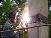 stock photo of collier  - The welder welds a metal plate of a pile - JPG