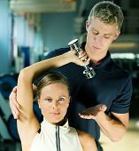 picture of lifting weight  - Young woman lifting a dumb - JPG