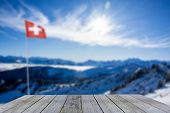 Wooden Shelf Display Against Swiss Flag Snow Covered Winter Mountain Panorama On A Sunny Day, Blue S poster