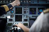 Pilots hand accelerating on the throttle in  a commercial airliner airplane flight cockpit during t poster