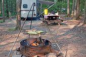 stock photo of trailer park  - Cooking on an outdoor grill with a picnic table and camping trailer in the background - JPG