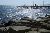Rocky Coastline, Glittering Sea And A Pier With Street Lamps And Silhouettes poster