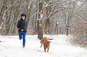foto of emo-boy  - Funky boy is having fun with his dog in the snow - JPG