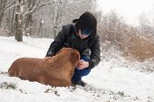stock photo of emo-boy  - Funky boy is having fun with his dog in the snow - JPG