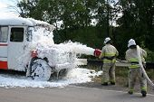 stock photo of decontamination  - firefighters in gas masks with foam extinguish a burning bus - JPG