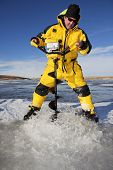 pic of auger  - Water floods over the ice as an ice fisherman drills through with an auger to make his fishing hole - JPG