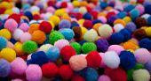 stock photo of pom poms  - Multicoloured pile of brightly coloured pom poms - JPG